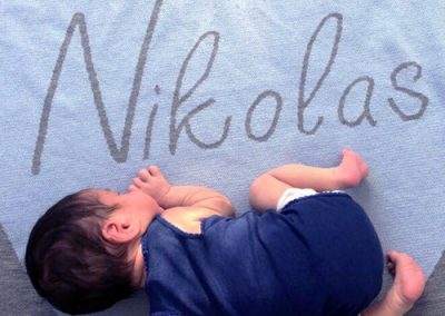 Baby sleeping on a pure wool personalised Branberry Blanket in a light blue, grey and white