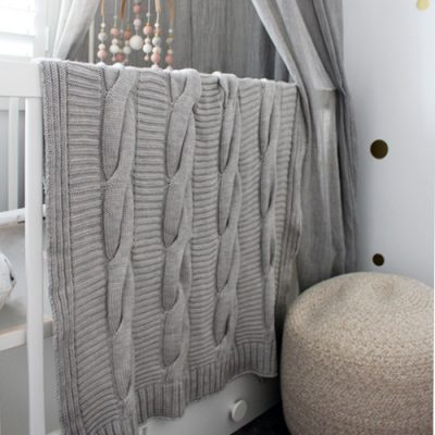 A white cot with a Branberry chunky light grey knitted pure wool cable blanket hanging over the edge of it