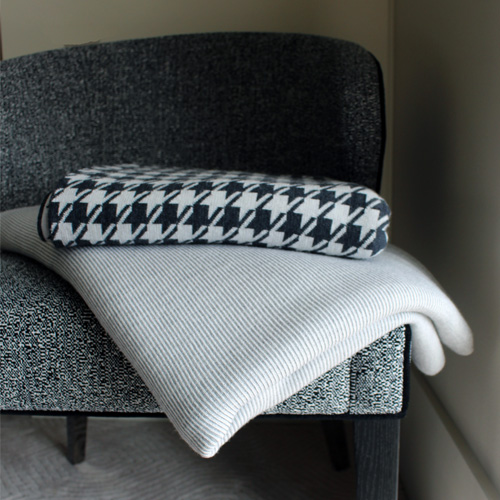 Branberry Pure Australian Merino wool throw blankets folded on a chair. A silver Bobbi blanket and a houndstooth blanket in grey