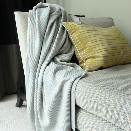 Branberry Pure Australian Merino Wool, Bobbie Throw Blanket in Silver draped over a couch.