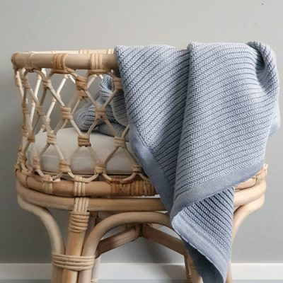 A Branberry cotton & wool cot blanket in grey hanging over a bassinet