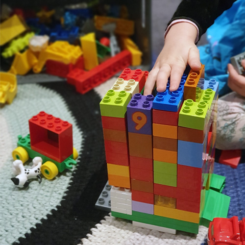 Fun & Free at home activities to entertain young children. A child sitting and playing with lego block. Building a tower