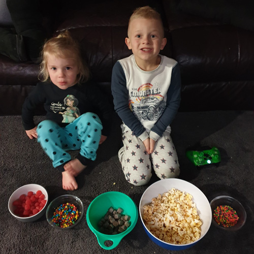 Fun & Free at home activities to entertain young children. Movies Night, A brother and sister sitting ready to watch a movie with their popcorn and lollies.