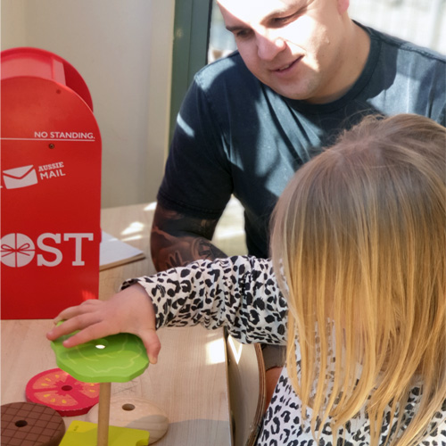 Fun & Free at home activities to entertain young children. Father and Daughter playing with a wooded stackable puzzle.