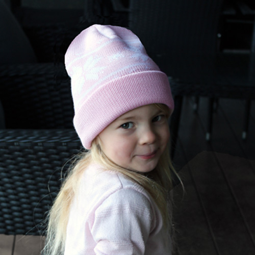 A young girl wearing an Australian Made, Australian Merino Wool Snowflake Beanie in Pink and White