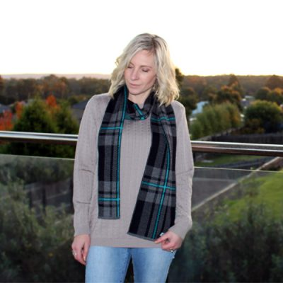 Lady wearing an Australian Made, Branberry Pure Merino Wool Tartan Scarf in Black, Grey and Aqua