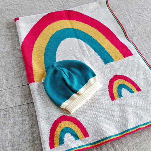 Flatlay of an Australian Made, Australian Merino Wool Rainbow Blanket in bright vibrant colours of pink, yellow and aqua with matching aqua Zest baby beanie