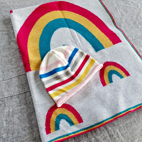 Flatlay of an Australian Made, Australian Merino Wool Rainbow Blanket in bright vibrant colours of pink, yellow and aqua with matching rainbow baby beanie