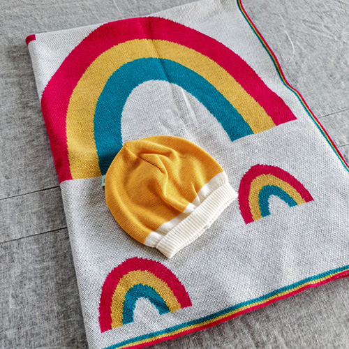Flatlay of an Australian Made, Australian Merino Wool Rainbow Blanket in bright vibrant colours of pink, yellow and aqua with matching Mango Zest baby beanie