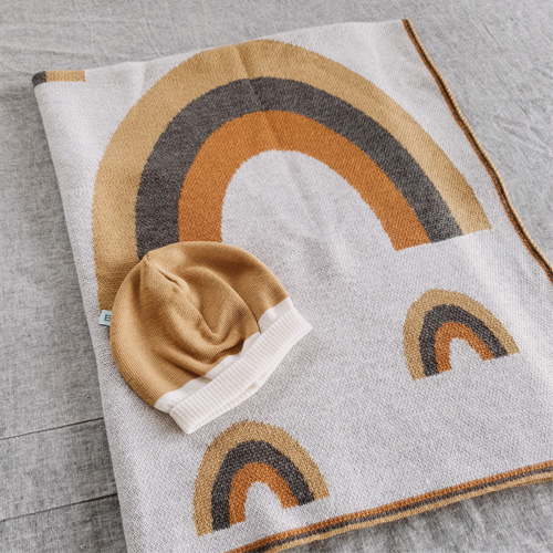Flatlay of an Australian Made, Australian Merino Wool Rainbow Blanket in Neutral Brown colours with a matching baby beanie