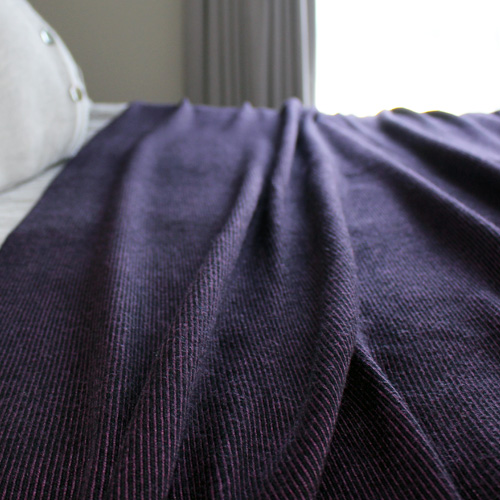 Branberry Pure Australian Merino Wool, Bobbie Throw Blanket in Blackcurrant draped over a king bed.