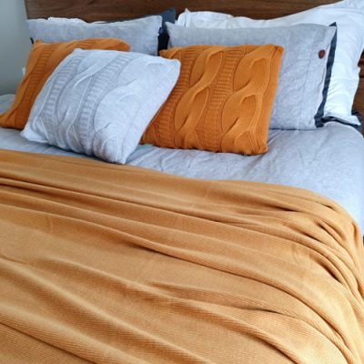 Branberry Pure Australian Merino Wool, Bobbie Throw Blanket in Copper draped over a king bed.