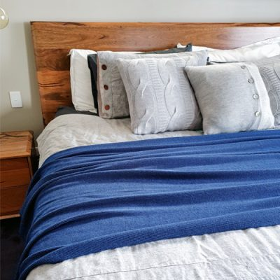 Branberry Pure Australian Merino Wool, Bobbie Throw Blanket in Denim Blue draped over a king bed.
