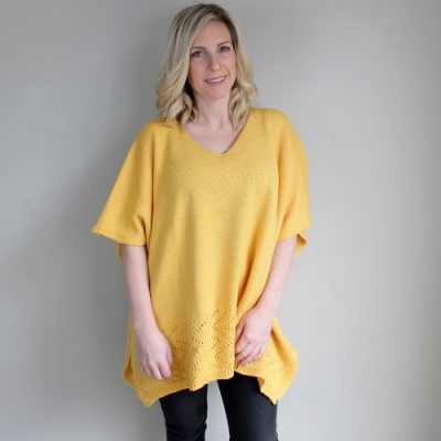 a lady standing and wearing a made in Ballarat, Branberry pure merino wool knitted poncho in mango yellow