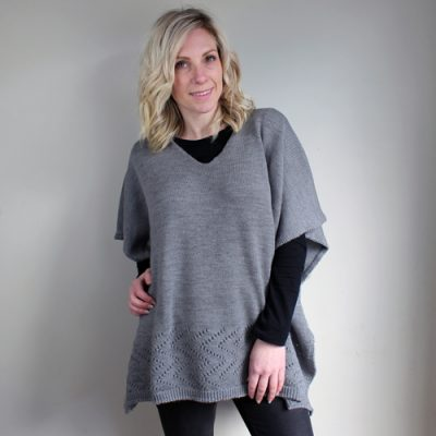 a lady standing and wearing a made in Ballarat, Branberry pure merino wool knitted poncho in wallaby grey