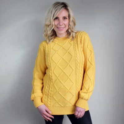 Lady wearing an Avery Aran Pure Wool Ladies Jumper in Mango Yellow