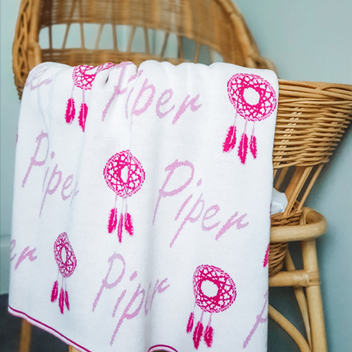 Branberry personalised pure merino wool name blanket in pink spread over a bassinet