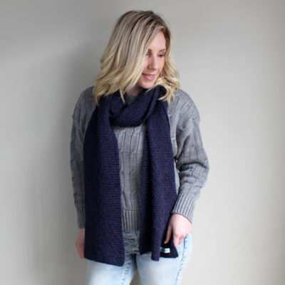 A lady wearing an Alpaca & Merino Wool Moss Scarf in Plum