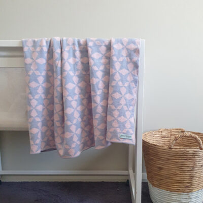 Branberry Pure Wool Star Gaze Blanket in Pink draped over a bassinet