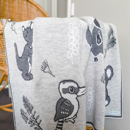 An Australian Animal knitted wool Branberry blanket in Quartz stone, monochrome tones hanging on a bassinet