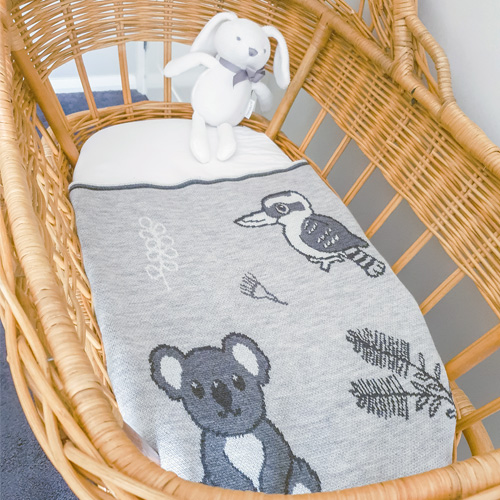 Top view of An Australian Animal knitted wool Branberry blanket in Quartz stone, monochrome tones placed in a bassinet