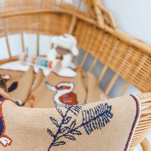 Close up view of An Australian Animal knitted wool Branberry blanket in earthy desert tones hanging on a bassinet